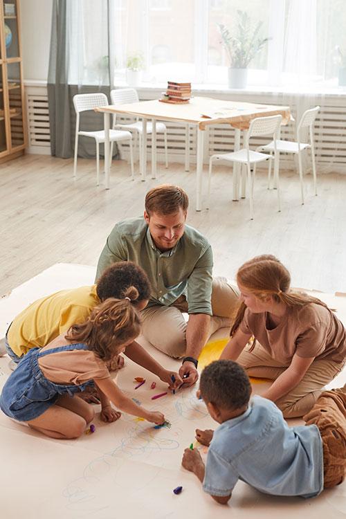 Erzieher malt mit Kindern auf dem Boden
