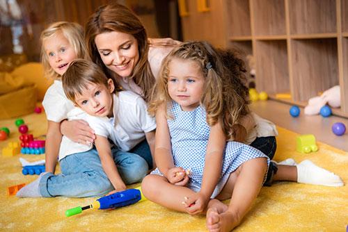 Erzieherin umarmt Kinder