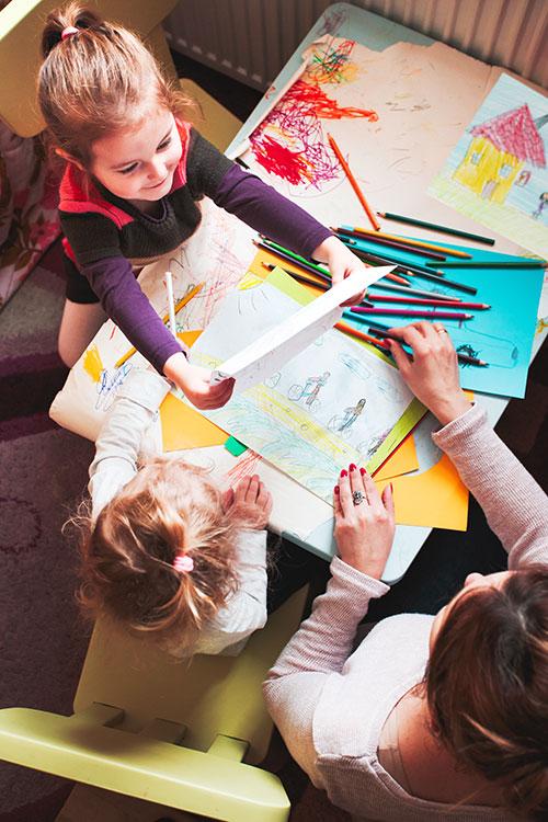Kinder malen Bilder mit Erzieherin